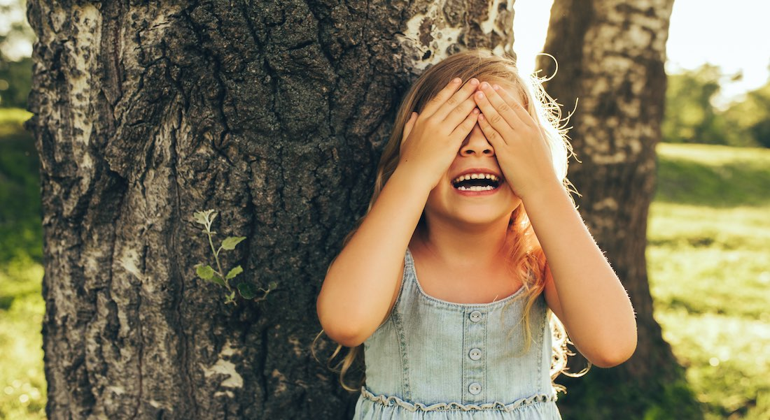 girl hiding in front of tree